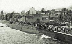 Festiva foto del recibimiento del Rey Alfonso XIII en el Parque de San Telmo con la Ermita de San Telmo en primer lugar y la calle La Marina, trasera de la calle Mayor de Triana, con las torres de la Catedral de Santa Ana al fondo, en Las Palmas de Gran Canaria, en abril de 1906
