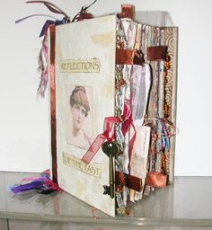 This altered book mixed media art features Victorian and 1920s themes, classic portraits and architectural imagery. The pages are hand-painted