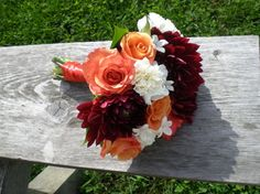 Perfect wedding bouquet for fall! Orange roses with burgundy dahlias. #orange #wedding #flowers by Envy Design