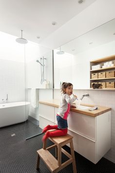 Maison De Gaspe bathroom in Montreal by la SHED architecture; has skylight and uses black hex tiles