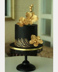 Black cake with gold accents and gold hand crafted orchids ~ we ❤ this! moncheribridals.com