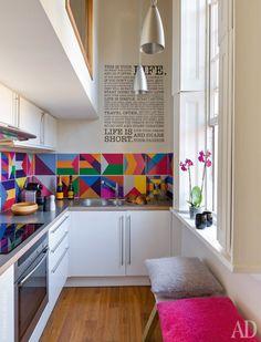 Piccola cucina moderna e allegra con paraschizzi in piastrelle con fantasie geometriche multicolore e pareti bianche