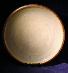 This attractive, decorative plate was wheel thrown and hand crafted by Buck Pottery in 1988. It is a beautifully glazed, green / gray piece with sky blue highlights. The edge contrasts in earthy brown. The back is signed Buck and also has 88 etched into it. It is a nice, sturdy piece of pottery.  More about Buck Pottery: http://www.buckpottery.com/story  Size: 11x11x0.75