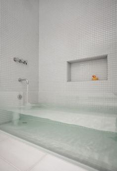 I would NOT want this bathtub, but it sure looks cool.  And I'm guessing with tile and glass as your materials, you could make it as long and deep as you wanted.  Definitely a plus.