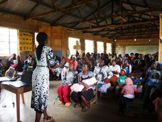 Community health worker Faith delivering mother-child wellness education to a room full of mothers and their under-5 children #publichealth #Kenya