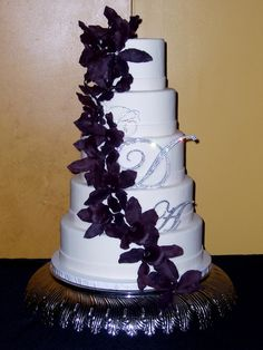 All white wedding cake with eggplant colored gumpaste flowers. Bride wanted really simple cake with gumpaste flowers to match dresses.
