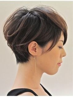 Short dark brown hair with long bangs.