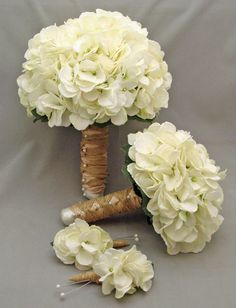 White Hydrangea, but real for the bridesmaids. Don't like the brown wrapping on the stems. Would want green either ribbons just the flowers exposed.