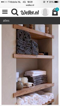 Een muur in de badkamer met houten planken.
