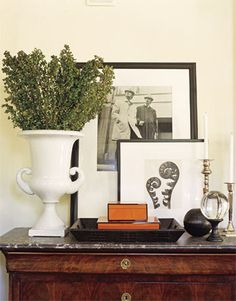 Beautiful monochrome vignette with interesting objects and a touch of orange. Note the classic elements; tray, boxes, small sculpture, framed pictures and vase.