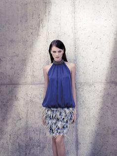 Original diseño con cuerpo azul y escote tipo halter y falda de plumas en varios colores