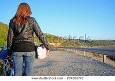 biker girl and motorcycle on the edge of the road at sunset
