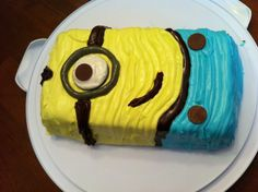 Despicable Me- minion cake Single layer chocolate cake Yellow, blue and brown icing (simply piped on with ziplock bag). 1/2 Oreo cookie 3 chocolate buttons