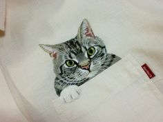 Kitty in a shirt pocket by embroidery artist Hiroko Kubota.