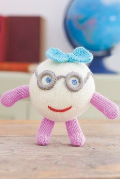 Quriky knitted round toy with glasses and bow on top of head. Shop this knitting pattern now at The Knitting Network