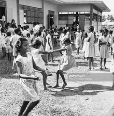 View of children playing in the yard of the Caroni Hindu School, Caroni County, Trinidad, Trinidad and Tobago, August 1956. Photo taken during the National Film Board of Canada's production of the 'New Nation in the West Indies' television series, a four-part introduction to the then recently formed Federation of the West Indies.