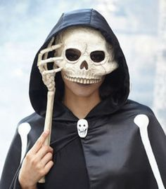 "opera skull mask What a ghoulish sight you'll make behind this intricately detailed mask. The creepy half-skull perches on a bone ""hand,"" and is sure to give a chill to those you encounter. Measures 17"". Resin and paper mâché. Imported. #42740"