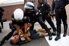 LAPD motorcycle officers detain a man in Los Angeles during a rally against the decision to not indict Darren Wilson and the LAPD's fatal shooting of Ezell Ford two days after Michael Brown was shot dead
