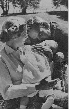 Prince Rainier III of Monaco kissing on of his children while his wife is sitting down who is holding the newest baby in her arms.