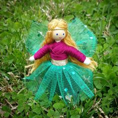 This beautiful little flower fairy is sure to delight any youngster or collector! Dressed in a lovely pink top and green skirt with a green floral glitter mesh overlay and gold belt she looks as thoug