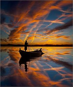 Boat on glassy water at sunset