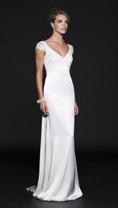 Jennifer Regan- Newtown. Gwenevieve is a V-neck narrow A-line wedding dress with deep V back and cap sleeves.  For the romantic, glamorous bride who loves a mix of beaded lace and rich silk satin. This flattering V-neck structured bodice with deep V back to the waist is hand draped and moulded with delicate beaded lace featuring a scallop edge is moulded to the silk satin bodice and cap sleeves.  The look is completed with the soft flow of the silk satin skirt and train. Fabrics – Silk satin