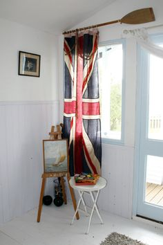 Flag curtain with an oar as a rod.  Great idea! Think I'd have this in a study as thick curtains and dark brown sofa