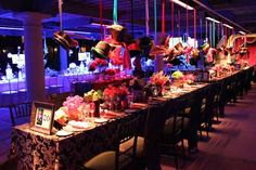 A view of the Mad Hatter table. Custom hats are suspended above; the event team later saw guests sporting the hats. The table is dressed in psychedelic paisley linen in onyx and platinum, accented with shots of tangerine, fuchsia and citron.