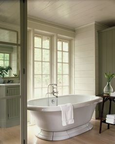 Chic Cottage Bathroom Features Walls Clad In Gray Green Shiplap Surrounding An Oval Freestanding Tub And Floor Mount Filler Next To A Rustic Console
