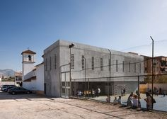 Circular perforations create spotlights in this concrete school extension
