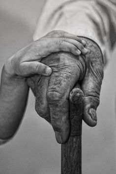 child's hand over old man's hand