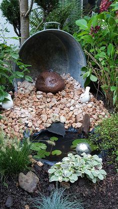 Alte Zinkwanne, Quellstein und kleine  Wanne eingegraben. Pumpe in die Wanne und Wasser fließt über die abgedeckte Teichfolie ins Becken zurück. Arbeitsaufwand 4 Stunden