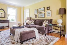 A cheerful traditional living room featuring yellow walls, a floral patterned rug, and a purple couch with a matching pouffe. #Mississauga #interiordesign #interiors #livingroom www.nicolainteriors.com
