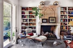 In the library of designer Isabel López-Quesada's home in Madrid, an Eames lounge chair and ottoman sit next to a 17th-century French chimneypiece; the side tables are vintage | archdigest.com