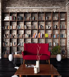exposed whitewashed brick wall, unique open-back bookcase in grid layout, striking oversized magenta chair, white track lighting, charcoal dark stained floor,,white accent pieces