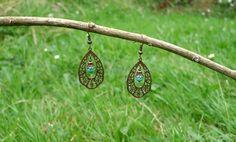 Boucles d'oreilles composées d'une estampe bronze, et d'une perle de verre turquoise agrémentée d'une calotte bronze. S'attachent par un…