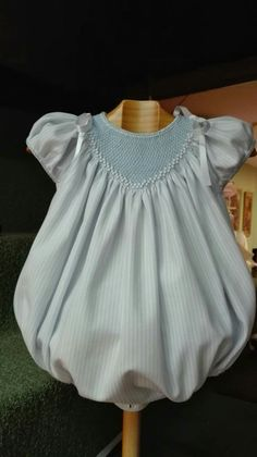 Cute blue baby bubble threaded with ribbon and tied at the shoulders.