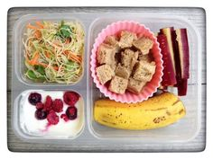This is what my daughters got for lunch today: Plain yogurt mixed with a little pure maple syrup and frozen berries, an experimental Asian brown rice noodle salad, peanut butter and honey on whole-wheat cut into squares with our new FunBites tool, part of a banana, and purple carrots.