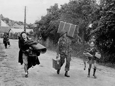 At Sainte-Mère-Eglise, Pfc Clayton Hayes of the 505th Battalion of the 82nd Division, helps a woman and her son to carry their things. Pfc Hayes was killed in Holland Sept. 20, 1944 during Operation Market Garden.