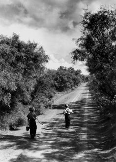 two children walking down a dirt road going fishing on a summer day, tx, us, june, 1952. photo by john dominis