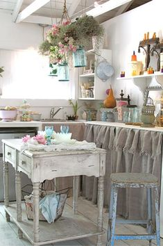 Vintage style white kitchen. Upper cabinets have been replaced with shelves and filled with collections. Check out that wonderful sideboard used as an island! Turquoise Mason jars are filled with pink flowers and hung from the ceiling beams. Adorable!