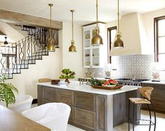 10 Kitchen Islands   Beth Webb Interiors creates a stylish moment with statement lighting in the form of four brass pendants over a beautiful wood island in front of an eye-catching backsplash. The room exudes warmth, while light neutrals and clean lines keep everything feeling fresh.