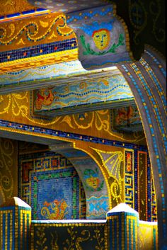 This is a close-up photograph taken of the Roman Pool at Hearst Castle in San Simeon, CA. It is a stunning room featuring an indoor pool covered floor to ceiling with one-inch colorful gold mosaic tiles. The design is styled after Roman pools and 5th Century Mausoleum mosaics.