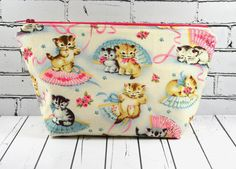 Kitsch Cats Makeup Bag. This listing is for a zipper pouch featuring a kitschy cat print. It is 100% cotton throughout, and has a pink zip and lining.. This bag has a very wide opening and would easil