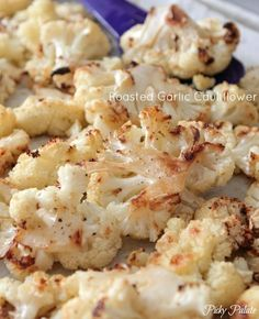 Roasted Garlic Cauliflower So simple! Cauliflower, spray of coconut oil, garlic salt and pepper and zap in the oven!