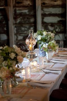 Antique oil lamps and mason jar arrangements as centerpieces.