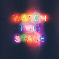 "A NEON SIGN THAT READS "" WATCH THIS SPACE."" THE LETTERS ARE DIFFERENT COLORS."