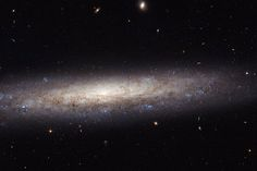 Spiral galaxy NGC 4206 lies roughly 70 million light-years away from Earth in the constellation of Virgo. This new Hubble Space Telescope shows the galaxy as it appears to us, edge-on. Streaks of dust partly obscure the central bulge. On the edges of the galaxy, scattered bluish clumps indicate areas where stars form. The bulge consists mainly of older, redder stars, and very little star formation takes place there.