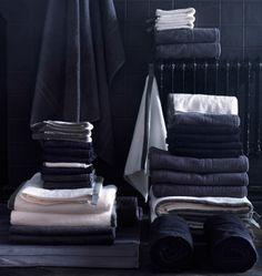 Närbild av en hög med svarta och vita handdukar i ett svartkaklat badrum.