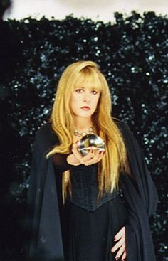 Stevie Nicks looking very witchy and holding a crystal ball.
